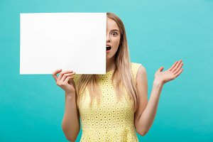 Portrait of amazed young blond woman holding blank sign with copy space on blue studio background. Showing shocked surprise face.