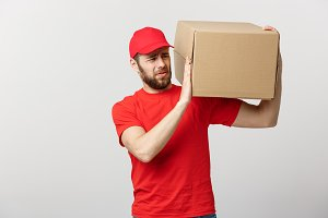Delivery Concept: handsome Delivery man with boxes, delivery, courier with worry facial expression. Isolated grey background.