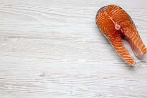 Raw salmon steak on white wooden