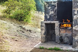 stone barbecue, with fire, outdoors.