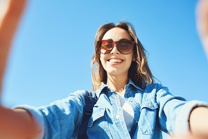 portrait of a young attractive woman making selfie on the blue sky background