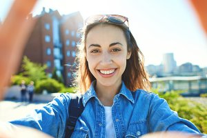 portrait of a young attractive woman making selfie on the city scape background