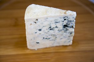 Blue cheese on wooden board. Side