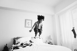 African kid jumping on the bed