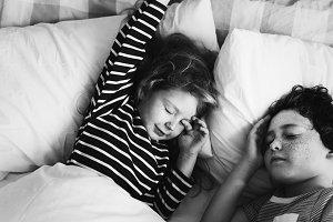 Caucasian siblings sleeping on bed
