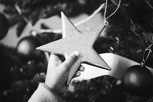 kid holding x'mas tree star ornament
