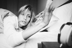 Sleepy woman turning off the alarm