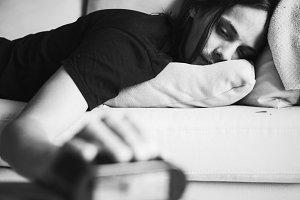 A sleepy man turning off the alarm
