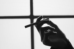 Greyscale style of cigarette in hand