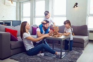 Happy family playing board games at home.