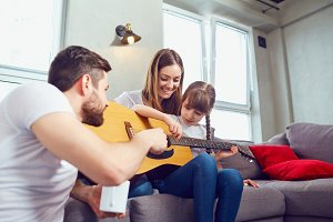 The family plays guitar together and sings songs.
