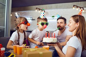 A happy family with a  cake celebrates a birthday party.