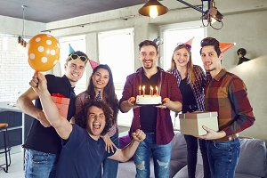 A group of friends with a torus with candles at a birthday party