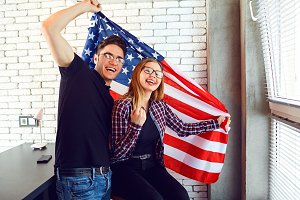 Young couple with an American flag smiling indoors.