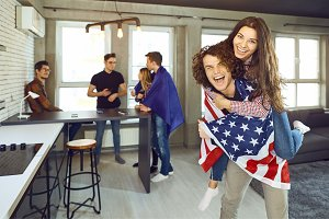 Friends with American flags are laughing indoors.
