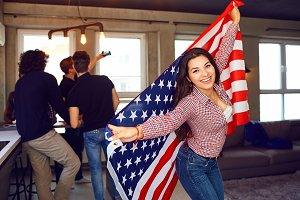Girl with a beautiful smile with the flag of america indoors.