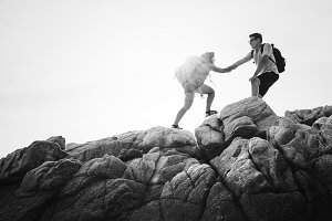 Friends help each other up mountain