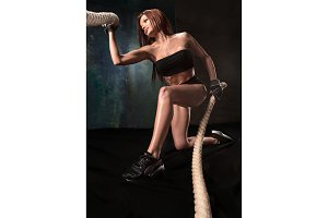 The strong young woman pulling rope at a gym
