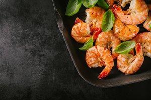 Grilled king prawns on pan on dark