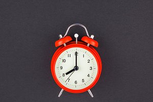 Red vintage alarm clock on dark