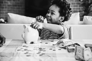 boy collecting money in piggy bank
