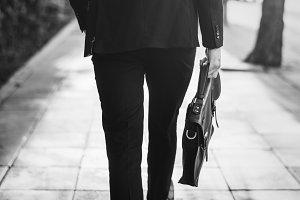 Businessman walking and holding bag