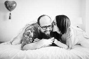 Wife kissing husband on bed