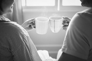 Couple celebrate with cups of coffee