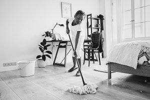 Young teen girl sweeping the floor