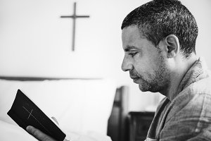 A man reading a bible alone