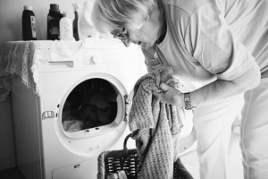 Elderly woman doing laundry at home