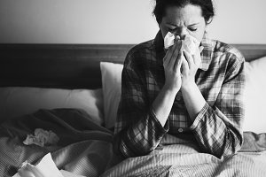 A sick woman sneezing in bed