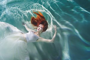 Underwater girl. Beautiful red-haire