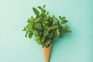 Waffle cone with fresh mint over blue background, vertical composition