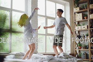 Slow motion of young married couple jumping and dancing on double bed in light room with large windows, happy people are having fun and laughing. Love and people concept.