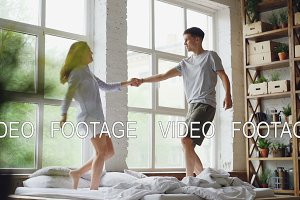 Slow motion of adorable loving couple dancing on bed and hugging together in modern light house. Happy young people, romance, entartainment and love concept.