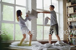 Slow motion of happy couple husband and wife having pillow fight on double bed, having fun and laughing. People, romantic relationship and entertainment concept.