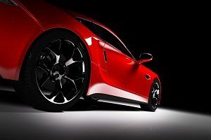 Side view of modern red sports car in a spotlight