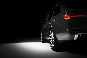 Back view of modern black SUV car in a spotlight