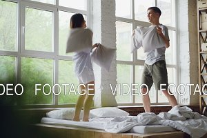 Slow motion of boyfriend and girlfriend jumping on double bed, fighting pillows and laughing together having fun in weekend morning. Free time and romance concept.