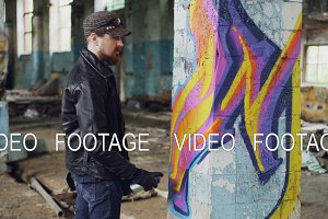 Professional graffiti painter is creating abstract image on large pillar inside abandoned building with spray paint. Young man is wearing leather jacket, cap and gloves.