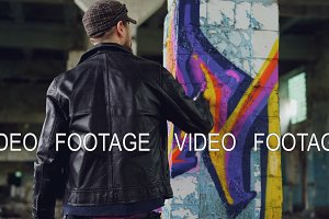 Rear view of male graffiti artist in leather jacket painting on damaged column inside empty industrial building. Young people, creativity, casual clothing and modern art concept.