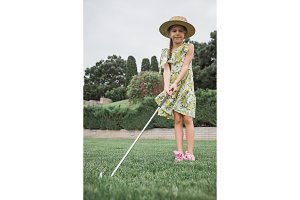 Little girl just swing golf ball on golf course fairway