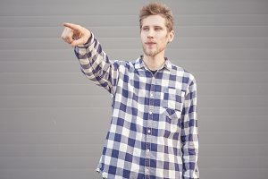 young serious bearded  man in checkered shirt points with finger