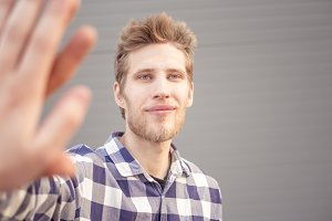 isolated young happy bearded  guy giving high five