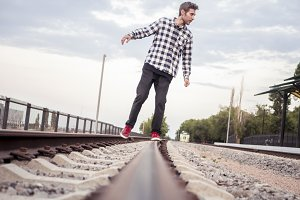 young bearded man in casual walking on a railway track towards the camera