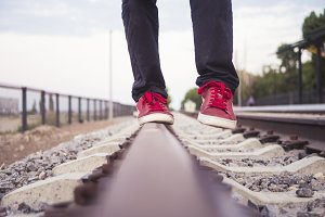 footsteps in red sneakers walking on a railway track