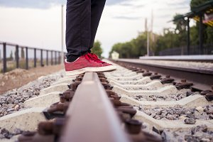 person in black pants and red sneakers standing still on the empty railway track