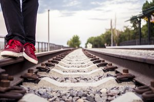 close up legs in red sneakers walking on a railway track