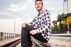 young bearded man looking forward sitting on a railway track, close up portrait